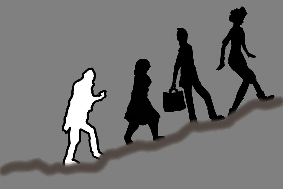 four figures, in silhouette, walk up a steep incline.